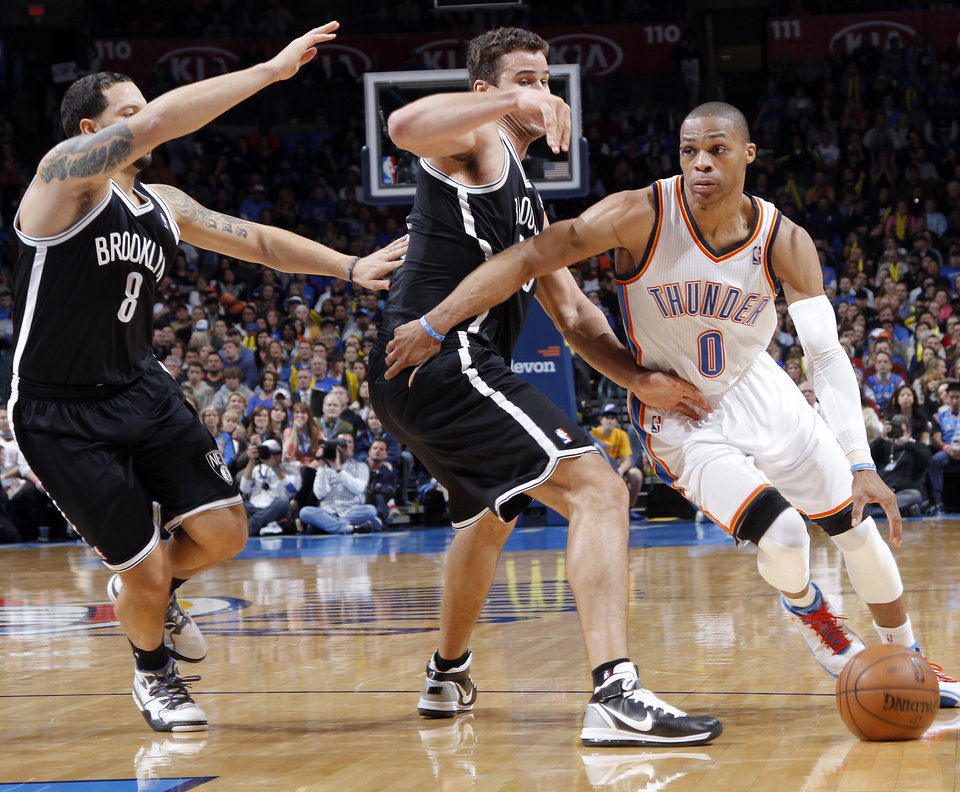 Photo - Oklahoma City's Russell Westbrook (0) drives past Brooklyn Nets' Kris Humphries (43) and Deron Williams (8) during the NBA basketball game between the Oklahoma City Thunder and the Brooklyn Nets at the Chesapeake Energy Arena on Wednesday, Jan. 2, 2013, in Oklahoma City, Okla. Photo by Chris Landsberger, The Oklahoman
