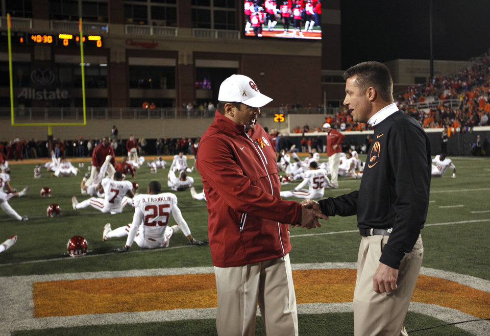 Oklahoma head coach Bob Stoops and Oklahoma State head coach Mike Gundy greet each other before the Bedlam college football game between the Oklahoma State University Cowboys (OSU) and the University of Oklahoma Sooners (OU) at Boone Pickens Stadium in Stillwater, Okla., Saturday, Dec. 3, 2011. Photo by Sarah Phipps, The Oklahoman