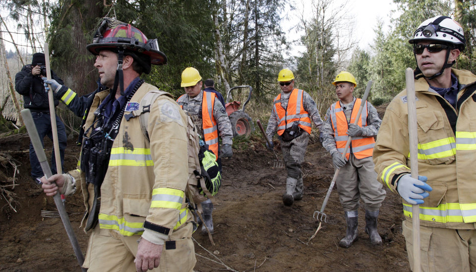 Photo - Searchers arrive to begin a shift at the scene of a deadly mudslide, Wednesday, April 2, 2014, in Oso, Wash. Officials have so far confirmed the deaths of 29 people, although only 22 have been officially identified in information released Wednesday morning by the Snohomish County medical examiner's office. (AP Photo/Elaine Thompson)
