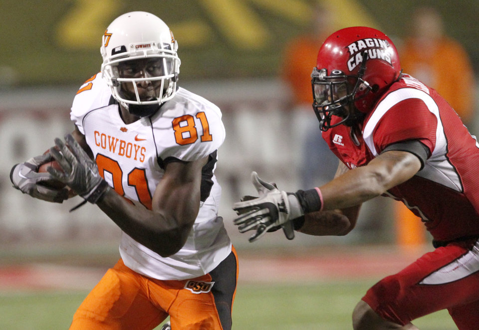 Photo - OSU's Justin Blackmon runs past  Louisiana-Lafayette's Devon Lewis-Buchanan during the football game between the University of Louisiana-Lafayette and Oklahoma State University at Cajun Field in Lafayette, La., Friday, October 8, 2010. Photo by Bryan Terry, The Oklahoman