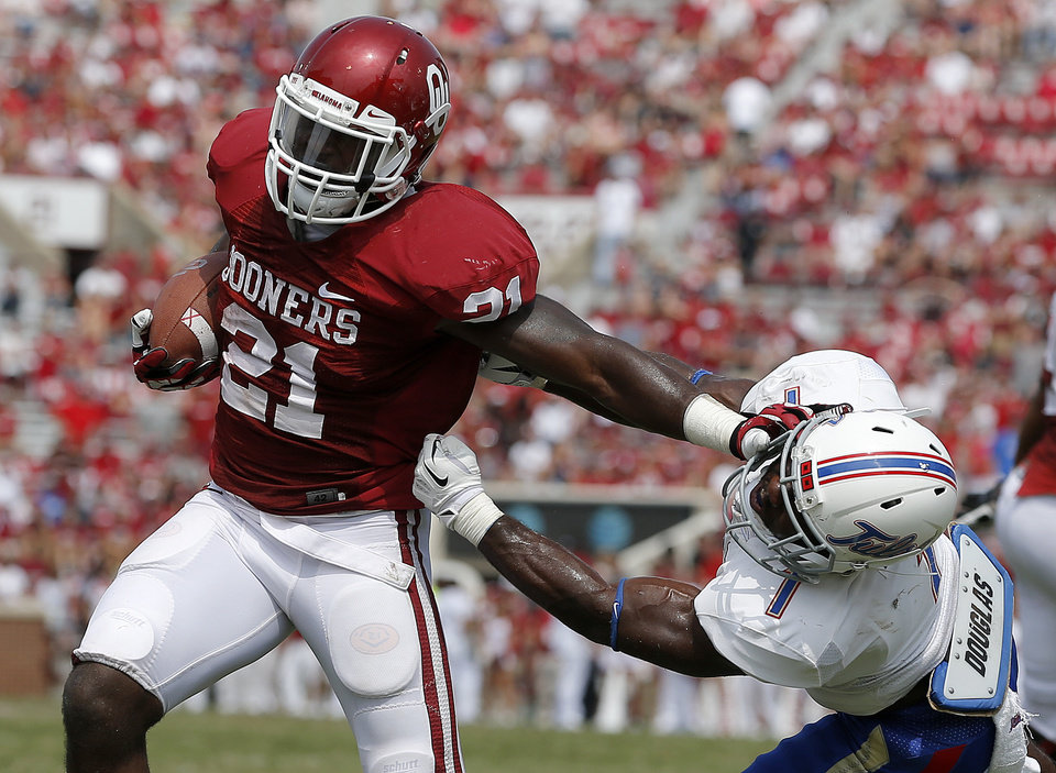 Photo - Oklahoma's Keith Ford (21) fights off Tulsa's Michael Mudoh (1) on his way to a touchdown during a college football game between the University of Oklahoma Sooners (OU) and the Tulsa Golden Hurricane at Gaylord Family-Oklahoma Memorial Stadium in Norman, Okla., on Saturday, Sept. 14, 2013. Oklahoma won 51-20. Photo by Bryan Terry, The Oklahoman