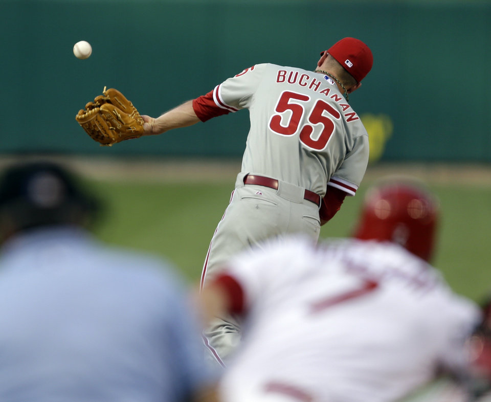 Photo - Philadelphia Phillies starting pitcher David Buchanan (55) cannot catch a ball hit back to him by St. Louis Cardinals' Matt Holliday during the first inning of a baseball game, Thursday, June 19, 2014, in St. Louis. Holliday was thrown out at first by Phillies shortstop Jimmy Rollins on the play. (AP Photo/Jeff Roberson)