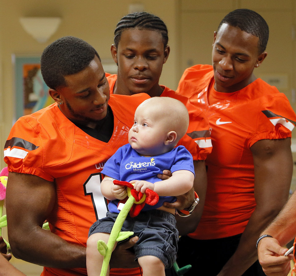 Oklahoma State's Brodrick Brown holds 1-year-old John Austin as Daytawion Lowe, middle, and Justin Gilbert look on during a visit by OSU football players to The Children's Hospital in Oklahoma City, Wednesday, July 11, 2012. Austin is a patient at The Children's Hospital. Photo by Nate Billings, The Oklahoman
