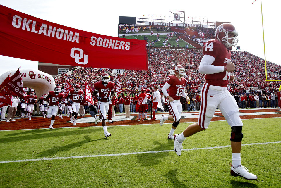 Photo - Sam Bradford (14) runs out onto the field with the team before the first half of the college football game between the University of Oklahoma Sooners (OU) and the Baylor University Bears at Gaylord Family-Oklahoma Memorial Stadium on Saturday, Oct. 10, 2009, in Norman, Okla. 