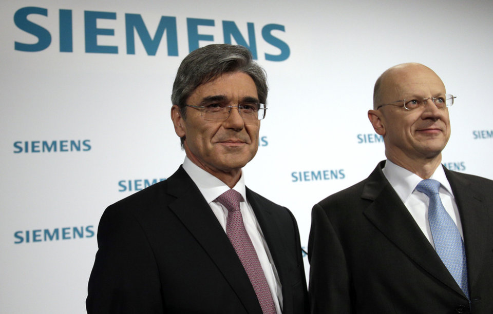 Photo - President and CEO of Siemens, Joe Kaeser, left, and the Chief Financial Officer of Siemens, Ralf P. Thomas, right, pose for photos before the company's joint semiannual press and analyst conference in Berlin, Germany, Wednesday, May 7, 2014. Kaeser is eliminating the sprawling company's four broad sectors overseeing its businesses, and will trim those business divisions from 16 to nine. Each division will get a profit margin target as Siemens aims to focus on fields where it can grow and earn the most. (AP Photo/Michael Sohn)