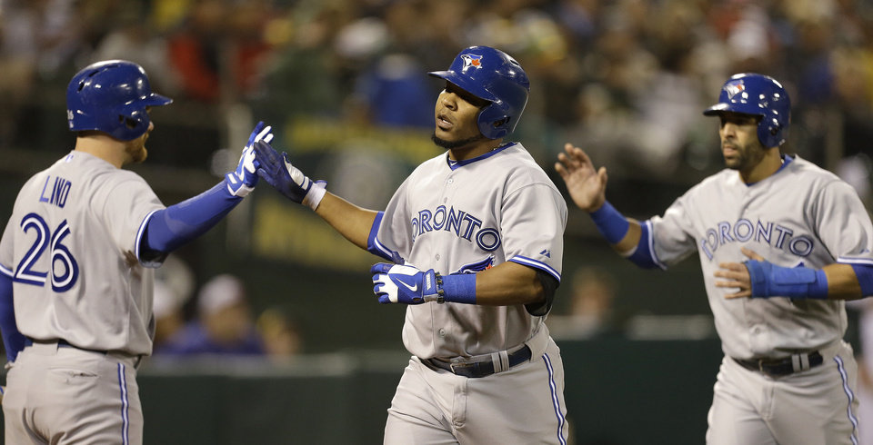 Photo - From left, Toronto Blue Jays' Adam Lind (26), Edwin Encarnacion, and Jose Bautista celebrate a two-run home run hit by Encarnacion in the sixth inning of a baseball game against the Oakland Athletics Monday, July 29, 2013, in Oakland, Calif. (AP Photo/Ben Margot)