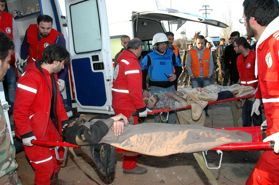 Photo - In this photo taken on Sunday Feb. 9, 2014, and released by the Syrian official news agency SANA, Syrian Arab Red Crescent members in red uniforms carry men injured from shelling into ambulances to evacuate them from the battleground city of Homs, Syria. A Syrian Red Crescent official says around 300 more people were evacuated Monday from besieged rebel-held neighborhoods of Syria's third-largest city, Homs. (AP Photo/SANA)