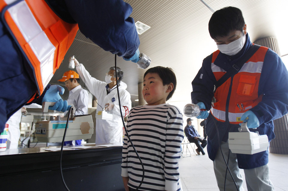 FILE - In this Friday, April 1, 2011 file photo, a boy is screened for radiation contamination before entering an evacuation center in Fukushima, Japan. Influential Japanese scientists who help set national radiation exposure limits have for years had trips paid for by the country�s nuclear plant operators to attend overseas meetings of the world�s top academic group on radiation safety. Some of these same scientists have consistently given optimistic assessments about the health risks of radiation, interviews with the scientists and government documents show. Their pivotal role in setting policy after the March 2011 tsunami and ensuing nuclear meltdowns meant the difference between schoolchildren playing outside or indoors and families staying or evacuating. (AP Photo/Wally Santana, File)