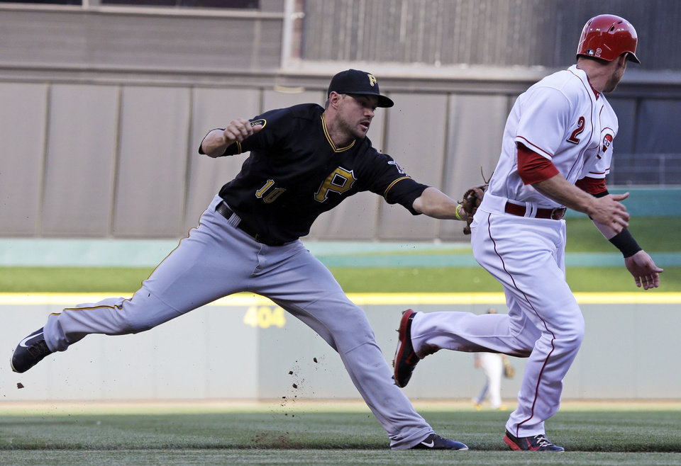 Photo - Pittsburgh Pirates shortstop Jordy Mercer (10) tags out Cincinnati Reds' Zack Cozart (2) after he was caught in a rundown in the first inning of a baseball game, Friday, July 11, 2014, in Cincinnati. (AP Photo/Al Behrman)