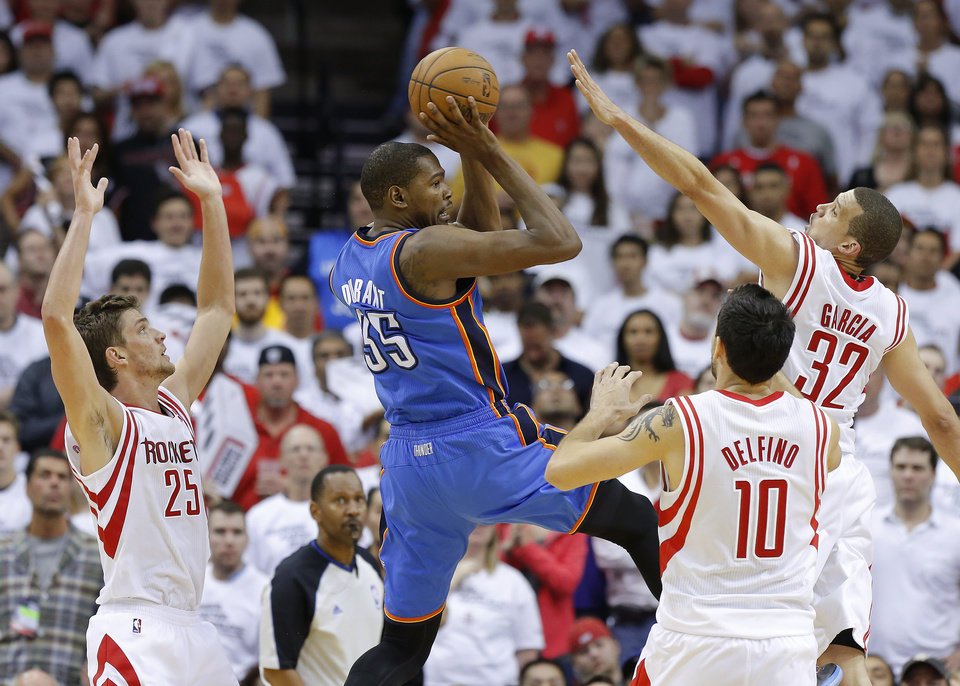 Photo - Oklahoma City's Kevin Durant (35) goes between Houston's Chandler Parsons (25), Carlos Delfino (10), and Francisco Garcia (32) during Game 3 in the first round of the NBA playoffs between the Oklahoma City Thunder and the Houston Rockets at the Toyota Center in Houston, Texas, Sat., April 27, 2013. Oklahoma City won 104-101. Photo by Bryan Terry, The Oklahoman