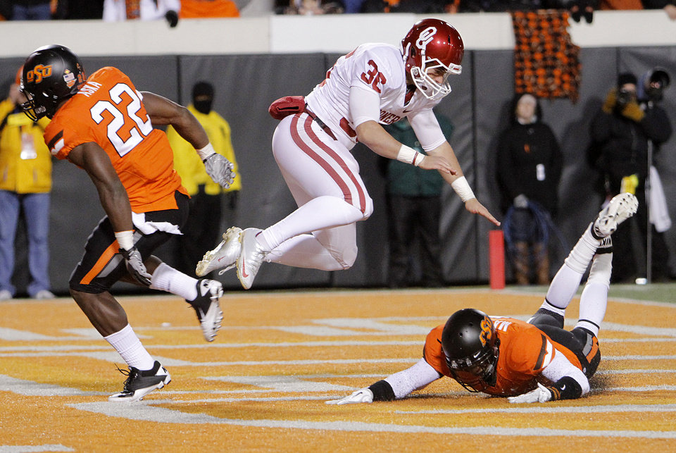 Photo - Oklahoma's Tress Way (36) is hit by Oklahoma State's Joe Aska Jr. (22) on a punt during the Bedlam college football game between the Oklahoma State University Cowboys (OSU) and the University of Oklahoma Sooners (OU) at Boone Pickens Stadium in Stillwater, Okla., Saturday, Dec. 3, 2011. Photo by Chris Landsberger, The Oklahoman
