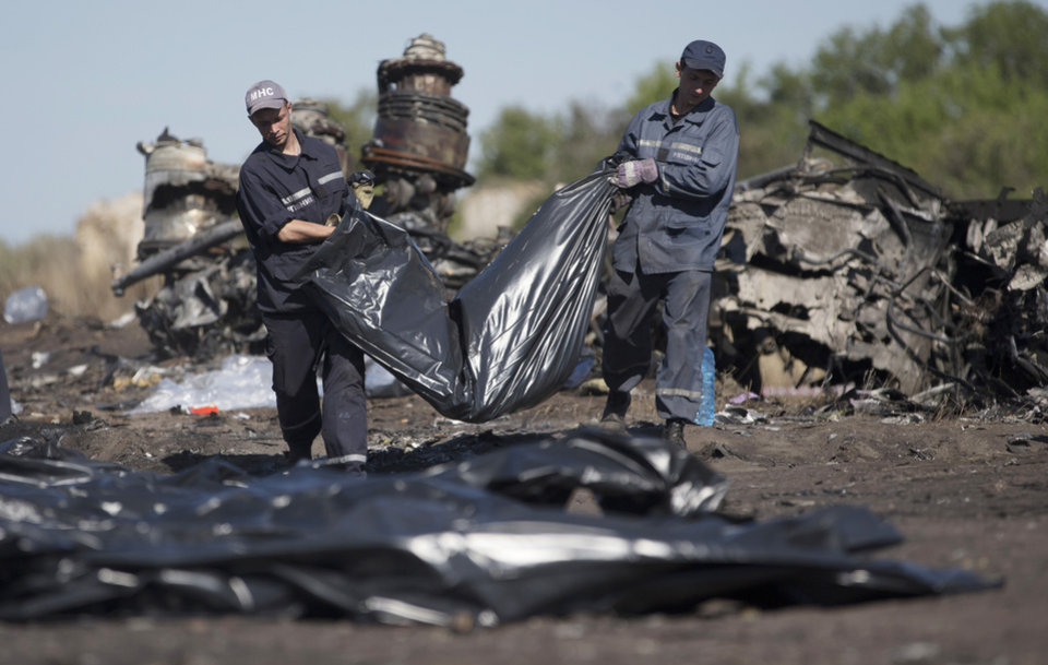 Photo - Ukrainian Emergency workers carry a victim's body in a bag at the crash site of Malaysia Airlines Flight 17 near the village of Hrabove, Donetsk region, eastern Ukraine, Monday, July 21, 2014. Another 21 bodies have been found in the sprawling fields of east Ukraine where Malaysia Airlines Flight 17 was downed last week, killing all 298 people aboard. (AP Photo/Dmitry Lovetsky)