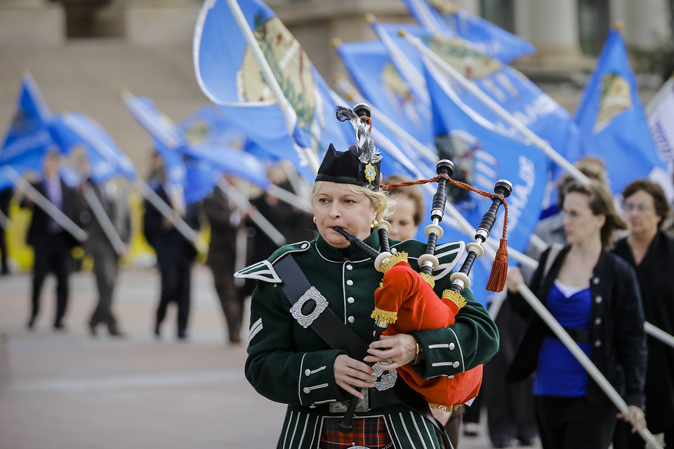 Bagpiper Michelle Brennan leads the procession of flags during the Field of Flags commemoration of victims of child abuse at the state Capitol on Monday, April 8, 2013, in Oklahoma City, Okla. Oklahoma legislators and supporters put up 41 Oklahoma state flags to commemorating a young victim of child abuse in the state.  Photo by Chris Landsberger, The Oklahoman