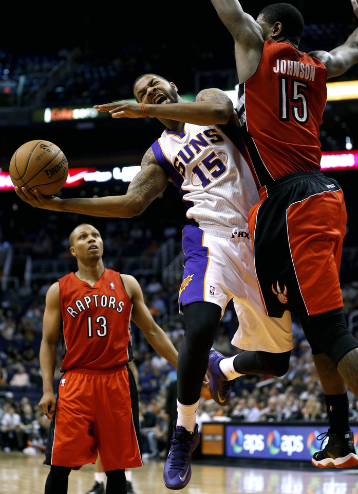 Photo - Phoenix Suns' Marcus Morris (15) is fouled by Toronto Raptors' Amir Johnson, right, during the second half of an NBA basketball game, Wednesday, March 6, 2013, in Phoenix.  (AP Photo/Matt York)
