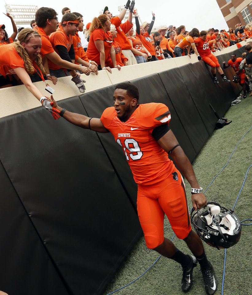 Photo - OSU's Brodrick Brown (19) celebrates with fans after a college football game between Oklahoma State University (OSU) and the University of Louisiana-Lafayette (ULL) at Boone Pickens Stadium in Stillwater, Okla., Saturday, Sept. 15, 2012. OSU won, 65-24. Photo by Nate Billings, The Oklahoman