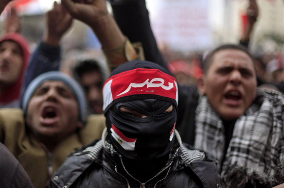 Photo - An Egyptian masked protester wears a head banner with Arabic writing that reads