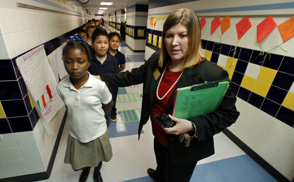 Photo - Arthur Elementary Principal Rhonda Schroeder, helps direct third-graders back to class from storm preparation assembly areas on Tuesday, April 1, 2014 in Oklahoma City, Okla.  Photo by Steve Sisney, The Oklahoman