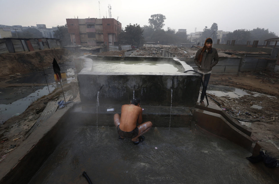 Anil Kumar Yadav, a daily wage worker, takes a bath early on a chilly morning in New Delhi, India, Tuesday, Jan. 8, 2013. North India continues to face below average weather conditions with dense fog affecting flights and trains. More than 100 people have died of exposure as northern India deals with historically cold temperatures. (AP Photo/ Saurabh Das)