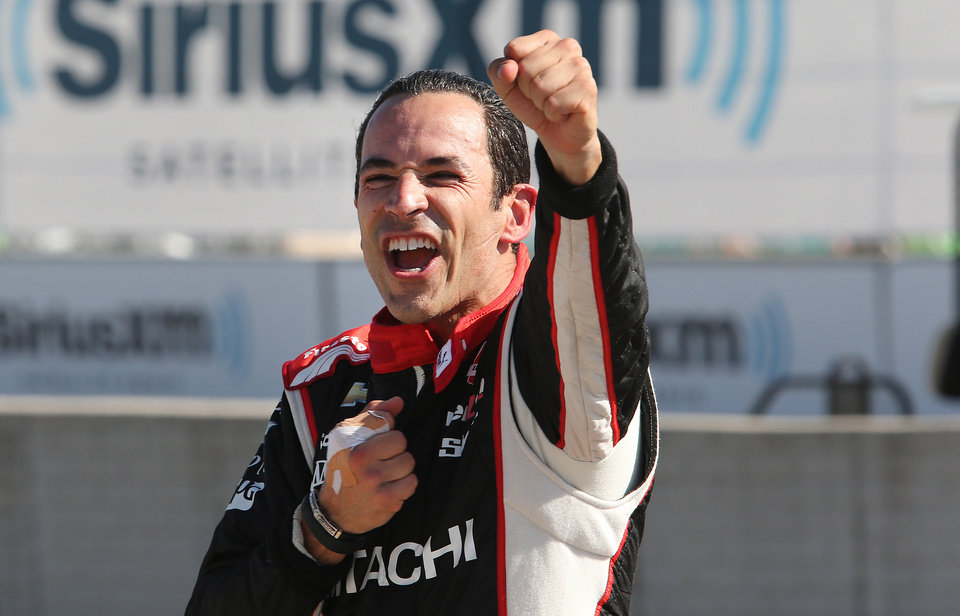 Photo - Helio Castroneves celebrates after winning the second race of the IndyCar Detroit Grand Prix auto racing doubleheader in Detroit Sunday, June 1, 2014. (AP Photo/Dave Frechette)