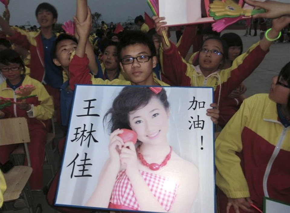 Photo - In this undated photo made available Monday, July 8, 2013, a supporter of Wang Linjia, holds up a photo of her with her name during a talent show at a school in Jiangshan city in eastern China's Zhejiang province. Chinese state media and Asiana Airlines have identified the two victims of the Asiana Airlines crash at San Francisco International Airport girls as Ye Mengyuan and Wang Linjia, students in Zhejiang, an affluent coastal province in eastern China.  (AP Photo) CHINA OUT