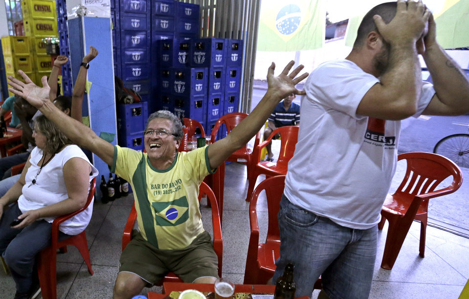 Photo - Brazil supporters react as they watch on the television the group A World Cup soccer match between Brazil and Mexico, at a bar in Indaiatuba, Brazil, Tuesday, June 17, 2014.(AP Photo/Shuji Kajiyama)