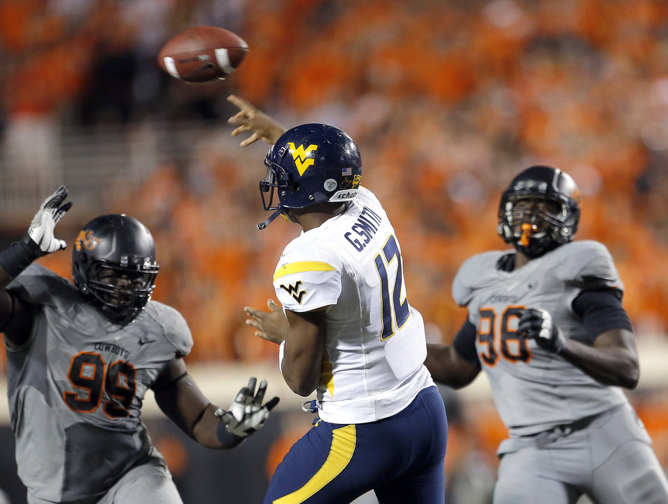 Oklahoma State\'s Calvin Barnett (99) and Davidell Collins (98) pressure West Virginia\'s Geno Smith (12) as he throws during a college football game between Oklahoma State University (OSU) and the West Virginia University at Boone Pickens Stadium in Stillwater, Okla., Saturday, Nov. 10, 2012. Photo by Sarah Phipps, The Oklahoman