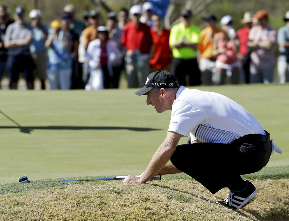 Photo - Jim Furyk lines up a putt on the fourth hole in his match against Rickie Fowler during the fourth round of the Match Play Championship golf tournament on Saturday, Feb. 22, 2014, in Marana, Ariz. (AP Photo/Ted S. Warren)
