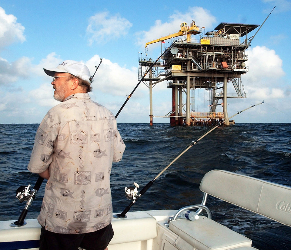 Photo - In in this May 9, 2003, file photo, angler Andy Hails, of Montgomery, Ala., checks the fishing lines on his boat as he trolls the Gulf of Mexico near a natural gas well near Gulf Shores, Ala.  AP Archive