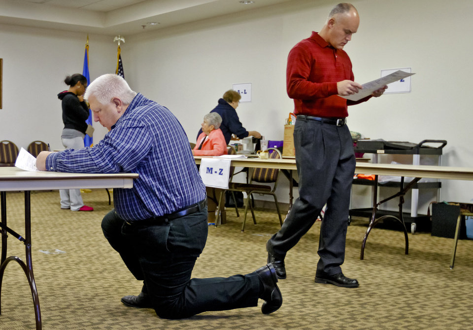 Photo - Voter Sheldon Davis, right, gives his ballot a final check before casting his vote during election day on Tuesday, Nov. 6, 2012, in Yukon, Oklahoma. Photo by Chris Landsberger, The Oklahoman