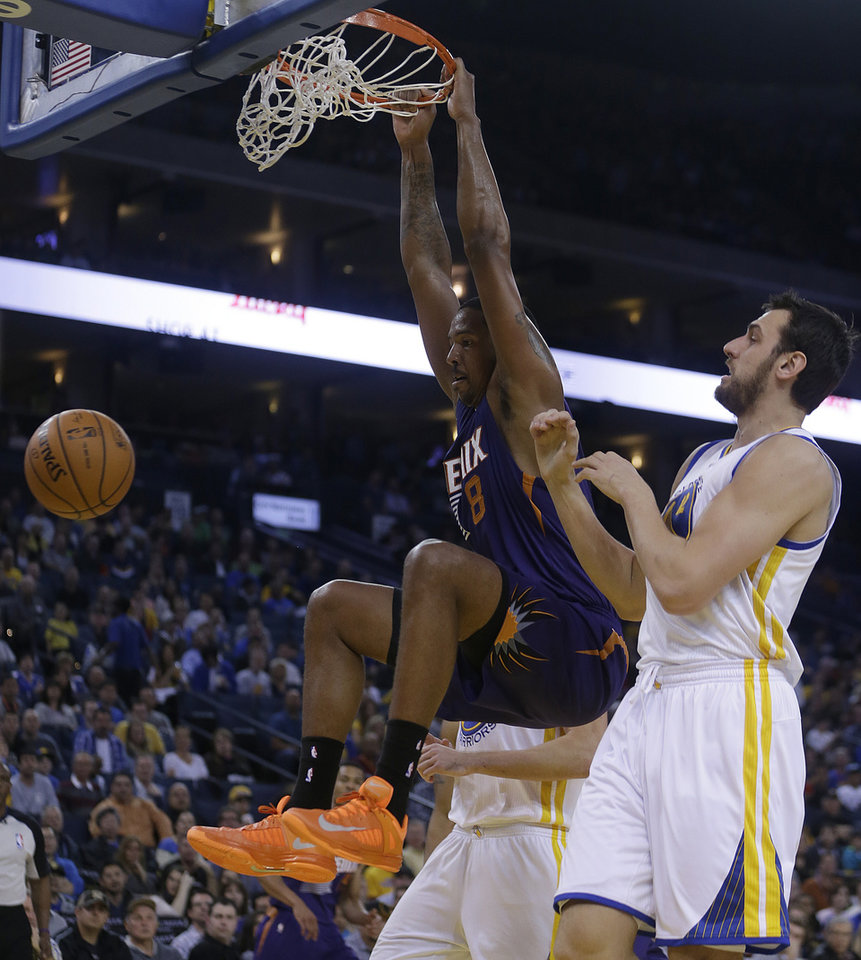 Photo - Phoenix Suns' Channing Frye (8) scores past Golden State Warriors' Andrew Bogut, right, during the first half of an NBA basketball game Sunday, March 9, 2014, in Oakland, Calif. (AP Photo/Ben Margot)