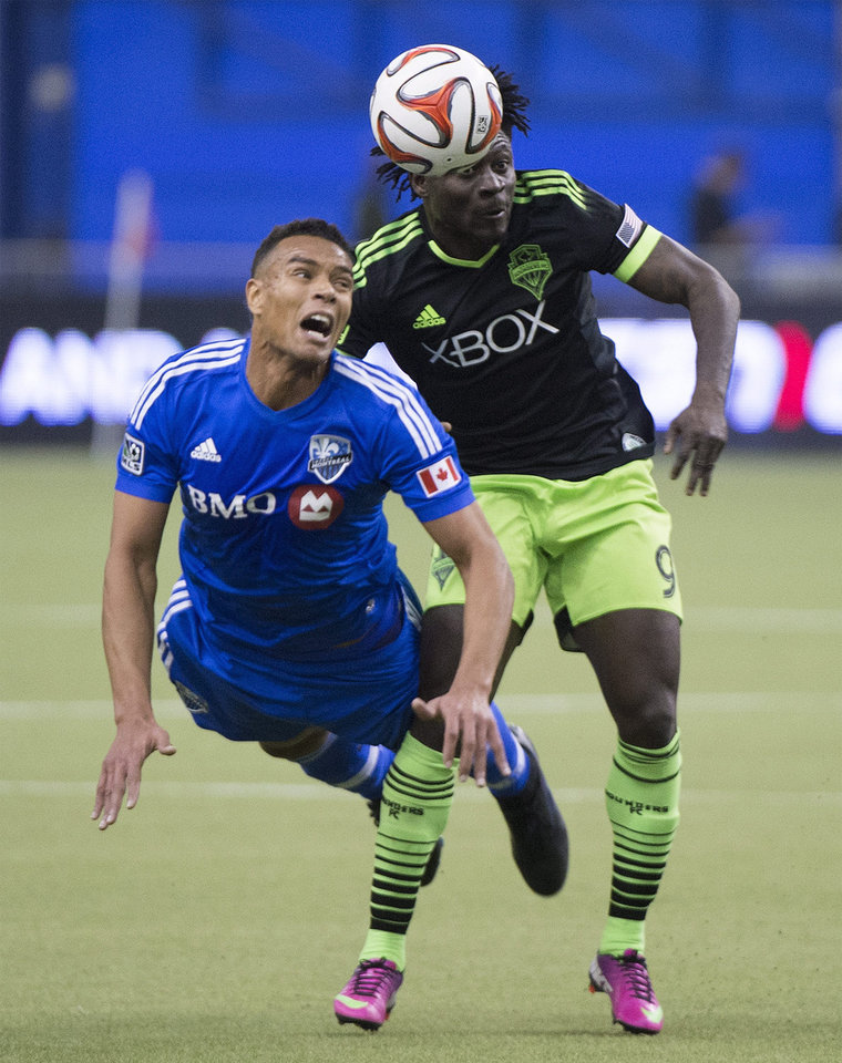 Photo - Montreal Impact's Matteo Ferrari, left, is challenged by Seattle Sounders' Obafemi Martins for the ball during second half MLS soccer action in Montreal, Sunday, March 23, 2014.(AP Photo/The Canadian Press, Graham Hughes)