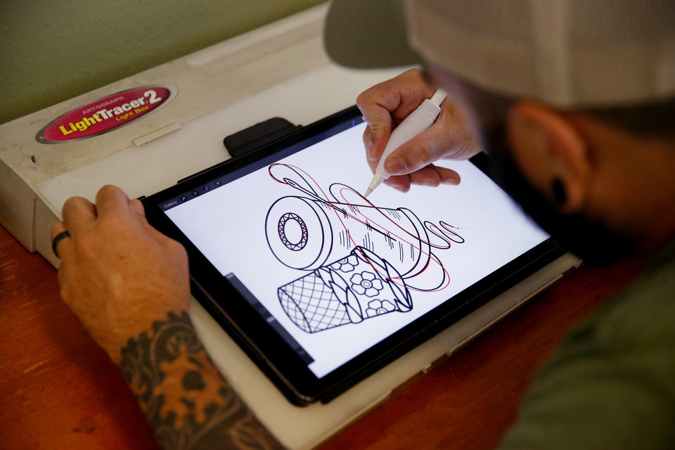 Photo - Wes Brooks, known as Lazlow, designs a tattoo inside Altered Images in Oklahoma City, Wednesday, June 26, 2019. [Bryan Terry/The Oklahoman]