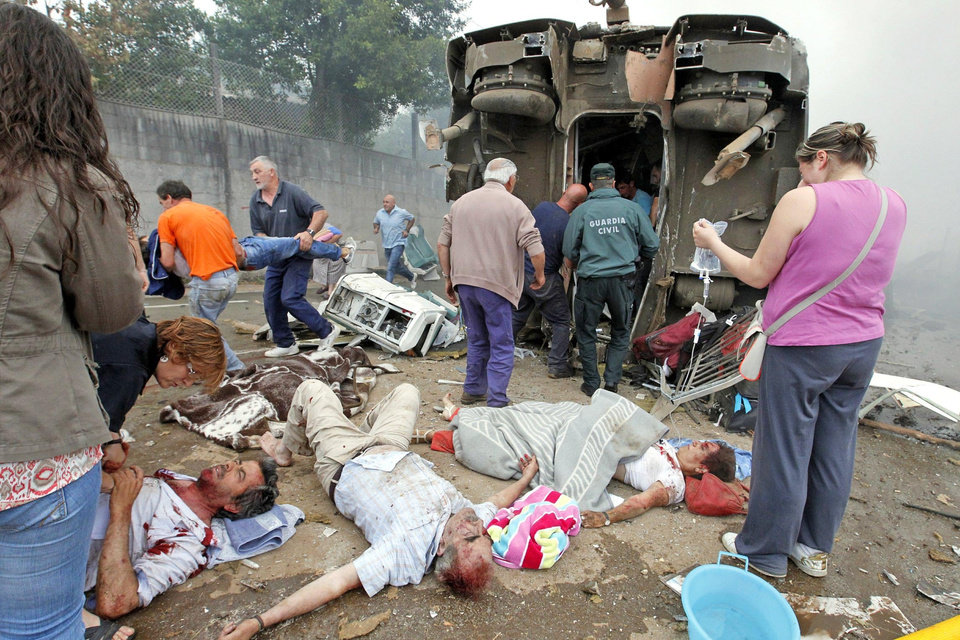Photo - In this photo taken on Wednesday July 24 2013,  victims are seen at the site of a train accident in Santiago de Compostela, Spain. Spanish police on Friday July 26 2013 detained the driver of a train that crashed in northwestern Spain, lowered the death toll from 80 to 78 and took possession of the