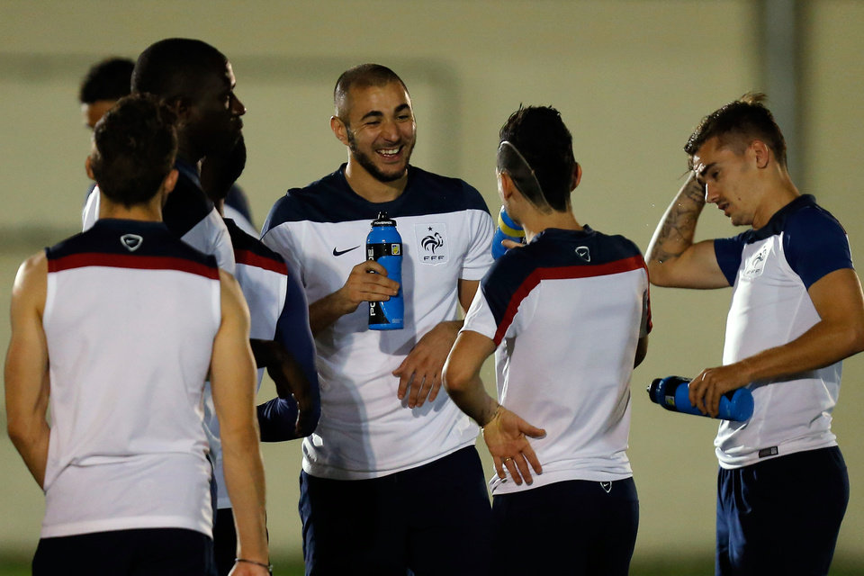 Photo - France's Karim Benzema, center, jokes with teammates during an official training session at the Joao Havelange Olympic stadium, in Rio de Janeiro, Brazil, Tuesday, June 24, 2014. France will play its next game against Ecuador in group E of the 2014 soccer World Cup. A draw is enough to guarantee top spot for France, and would also send Ecuador through to the next round if Switzerland fails to beat Honduras in the other match. (AP Photo/David Vincent)