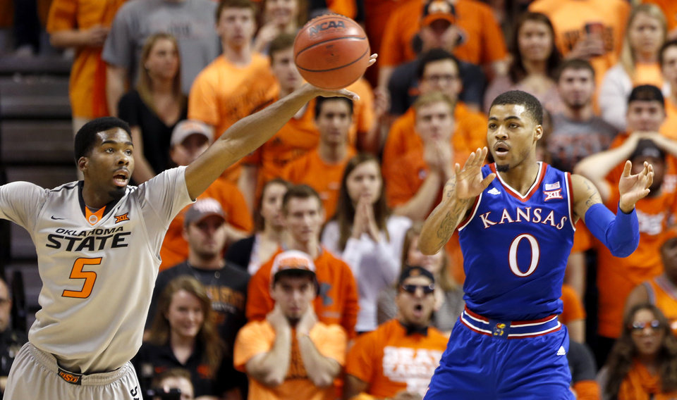 Photo - Oklahoma State's Tavarius Shine (5) steals a pass intended for Kansas' Frank Mason III (0) during the men's college basketball game between Oklahoma State University and the University of Kansas at Gallagher-Iba Arena in Stillwater, Okla.,  Saturday, Feb. 7, 2015. OSU won 67-62. Photo by Sarah Phipps, The Oklahoman