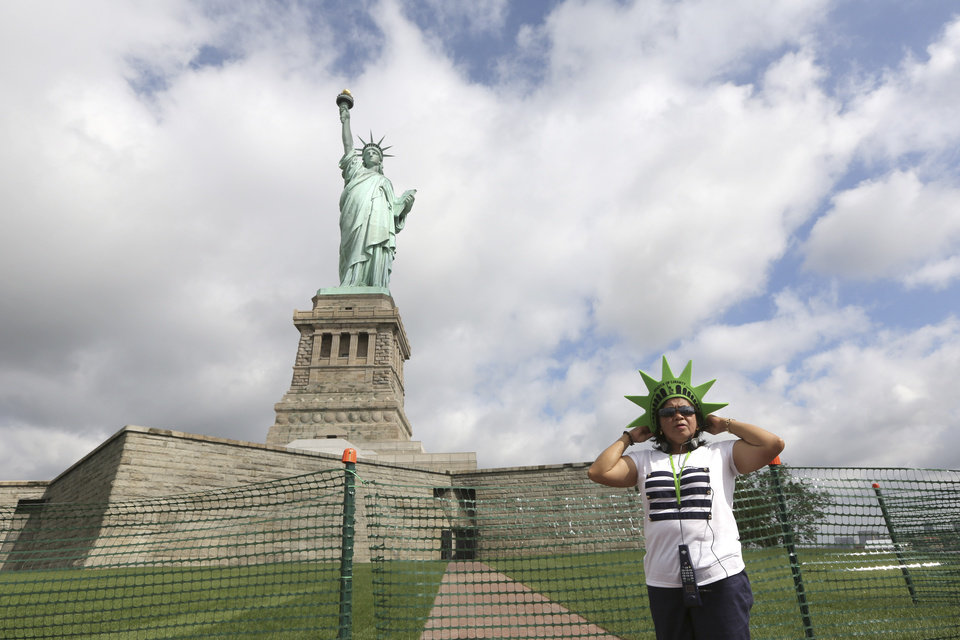 Leticia Baes, of the Phillipines, poses for a photo at the bases of the Statue of Liberty, Thursday, July 4, 2013 at  in New York. The Statue of Liberty finally reopened on the Fourth of July months after Superstorm Sandy swamped its little island in New York Harbor as Americans across the country marked the holiday with fireworks and barbecues. (AP Photo/Mary Altaffer)