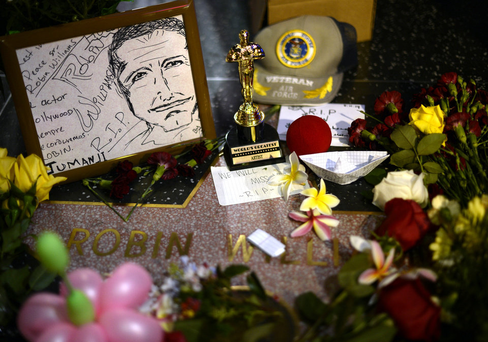 Photo - Flowers are placed in memory of actor/comedian Robin Williams' Walk of Fame star in the Hollywood district of Los Angeles Monday, Aug. 11, 2014. Williams, the Academy Award winner and comic supernova whose explosions of pop culture riffs and impressions dazzled audiences for decades and made him a gleamy-eyed laureate for the Information Age, died Monday in an apparent suicide at his San Francisco Bay area home. He was 63. (AP Photo/Kevork Djansezian)