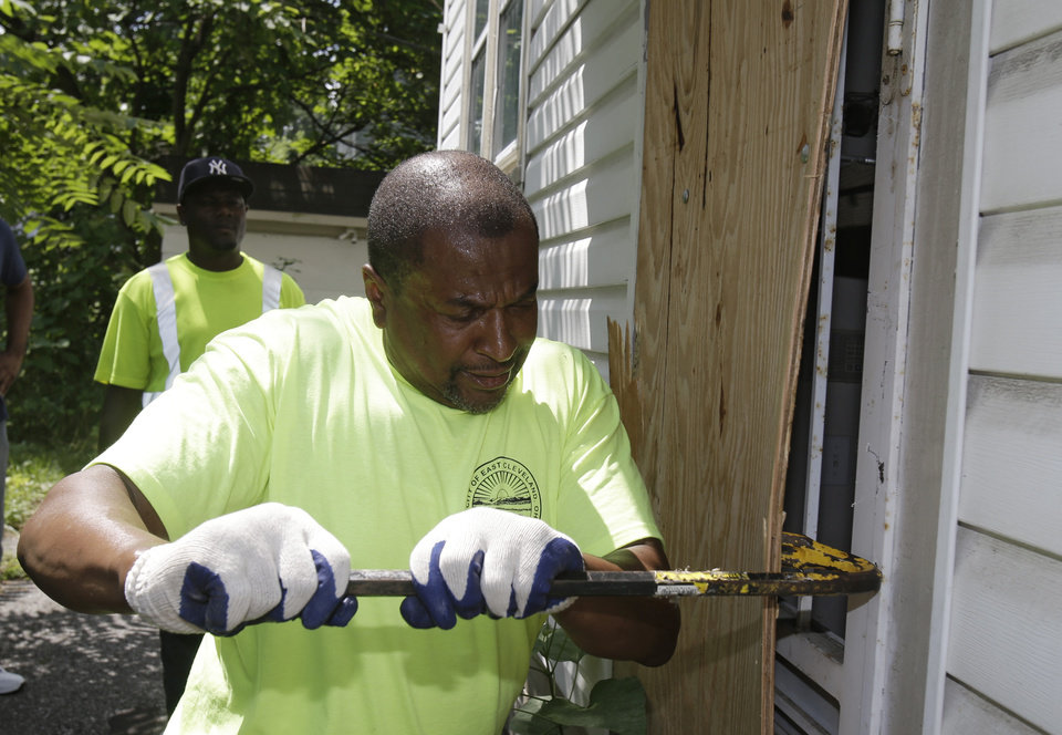 Photo - City of East Cleveland service department employee Ray Allen breaks into an abandoned house so searchers can enter Sunday, July 21, 2013, in East Cleveland, Ohio. Police Chief Ralph Spotts told volunteers checking vacant houses in a neighborhood where three bodies were found wrapped in plastic bags that he believes there could be one or two more victims. (AP Photo/Tony Dejak)
