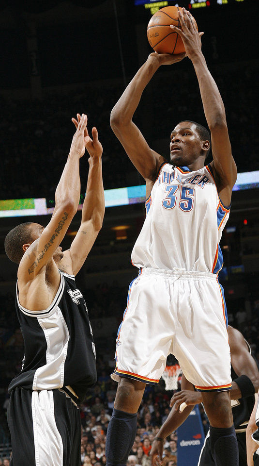 Photo - The Thunder's Kevin Durant (35) shoots the ball over the Spurs' George Hill (3) during the first half of the NBA basketball game between the Oklahoma City Thunder and the San Antonio Spurs at the Ford Center on Monday, March 22, 2010, in Oklahoma City, Okla.  Photo by Chris Landsberger, The Oklahoman ORG XMIT: KOD