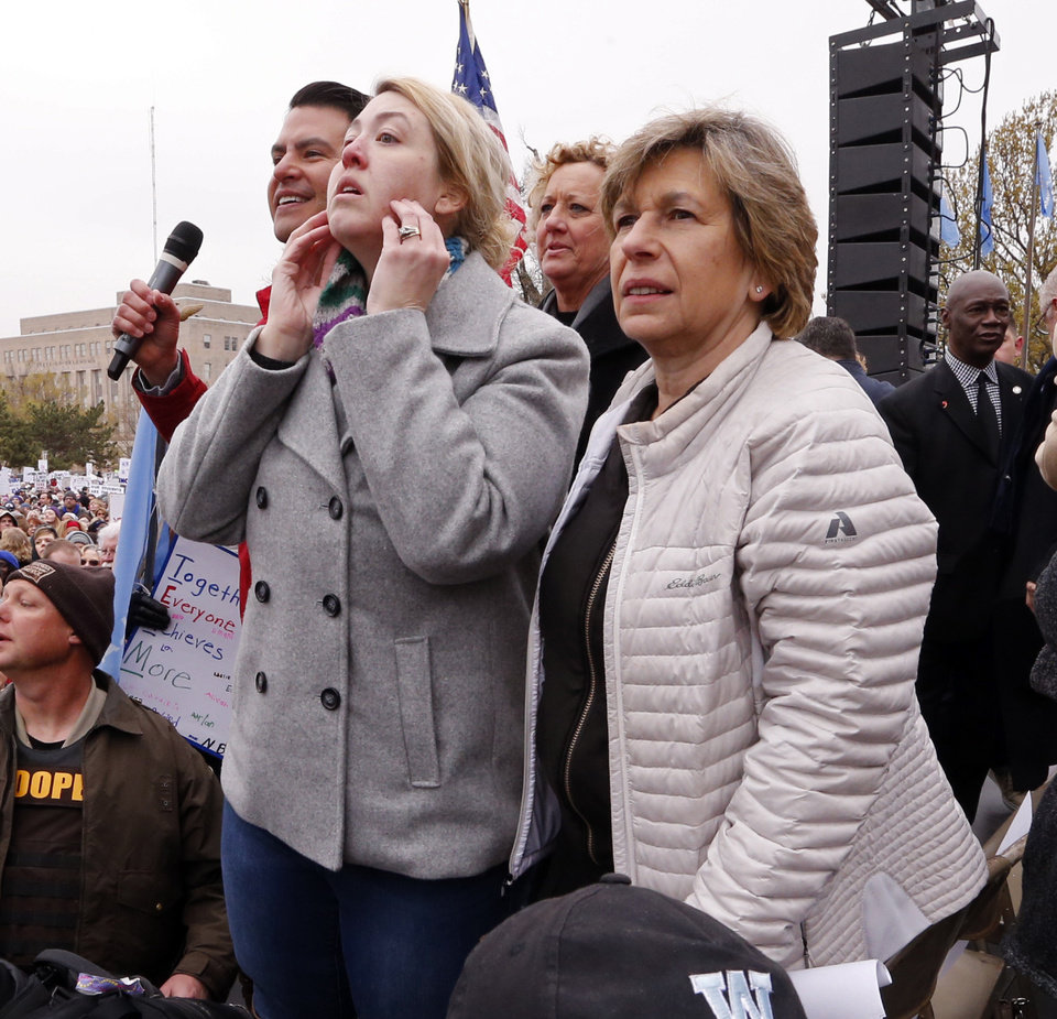 Photo - Kelly Lisenbee, Edmond, (center) stands on stage before the Oklahoma teachers rally and pleads for the crowd to find her lost son Ben, 8, at the State Capitol on Monday, April 2, 2018 in Oklahoma City, Okla.  Photo by Steve Sisney, The Oklahoman