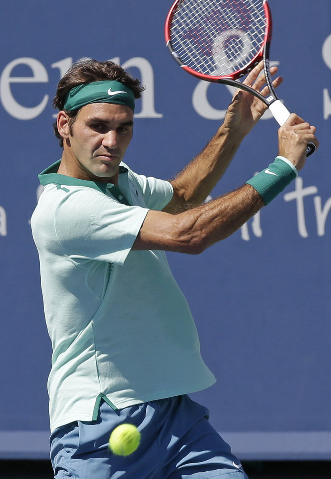 Photo - Roger Federer, from Switzerland, eyes a backhand against Vasek Pospisil, from Canada, during a match at the Western & Southern Open tennis tournament, Wednesday, Aug. 13, 2014, in Mason, Ohio. (AP Photo/Al Behrman)