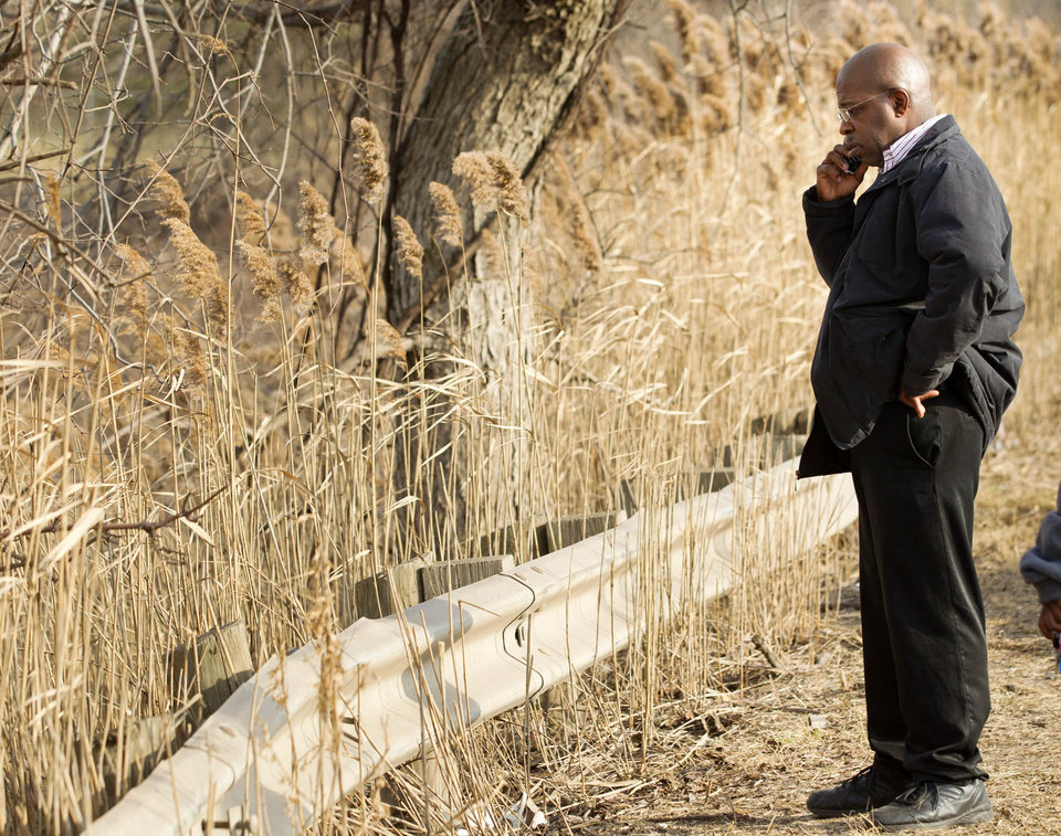 Photo - Derrick Ray, the father of Daylan Ray, talks on his phone at the crash site that claimed the life of his son and five others on Park Ave. in Warren, Ohio on Sunday, March 10, 2013. (AP Photo/Scott R. Galvin)