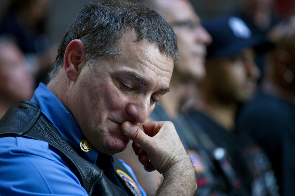 Photo - Retired FDNY Marshal, Ernie Medaglia, of Bronxville, N.Y., who was at the attacks at the World Trade Center on Sept. 11, 2001, is emotional as he listens to New York Gov. Andrew Cuomo at a ceremony near the 9/11 Memorial honoring first responders and FDNY Rescue 1 on the 12th anniversary of the attacks on the World Trade Center in New York Wednesday, Sept. 11, 2013. (AP Photo/Craig Ruttle)