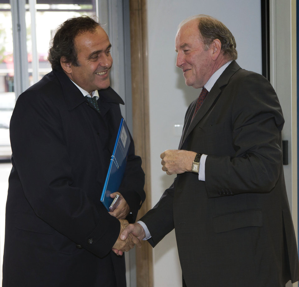 Photo -   UEFA President Michel Platini, left, is welcomed by President of the EURO 2016 organizing committee Jacques Lambert, right, for a meeting to prepare the European Championship in France at the headquarters of the French Football Federation in Paris, Tuesday, Oct. 23, 2012. (AP Photo/Michel Euler)