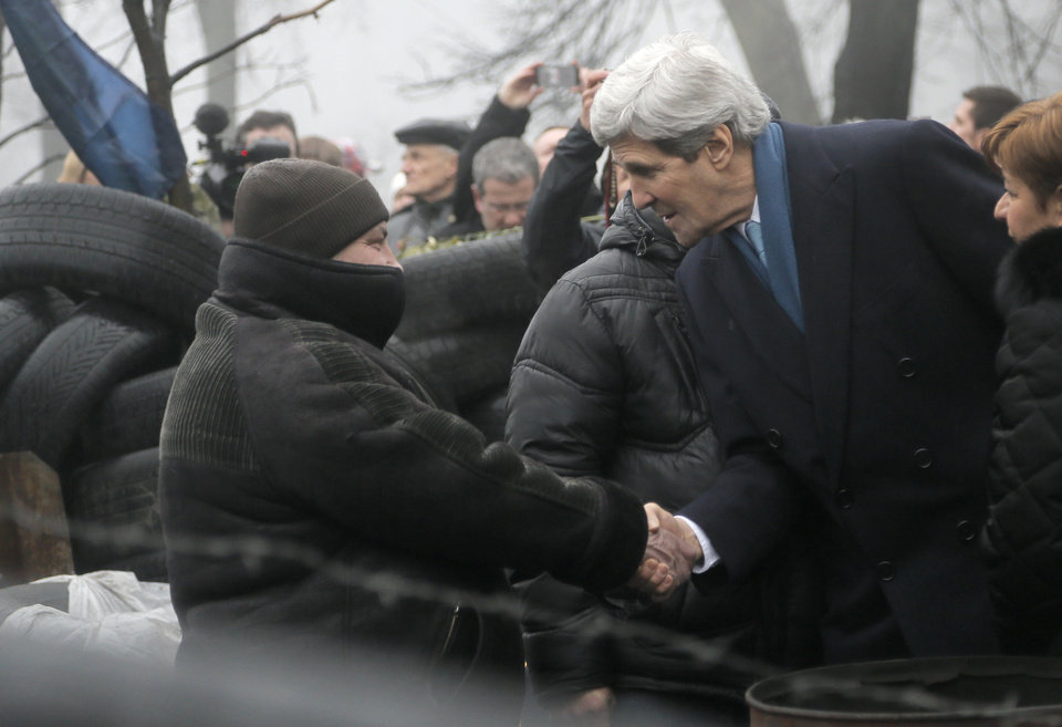 Photo - U.S. Secretary of State John Kerry, right, shakes hands with a Ukrainian protester at the barricades in Kiev, Ukraine, Tuesday, March, 4, 2014.  Kerry arrived in Kiev in an expression of support for Ukraine's sovereignty, and the EU threatened a raft of punitive measures as it called an emergency summit for Thursday. (AP Photo/Efrem Lukatsky)
