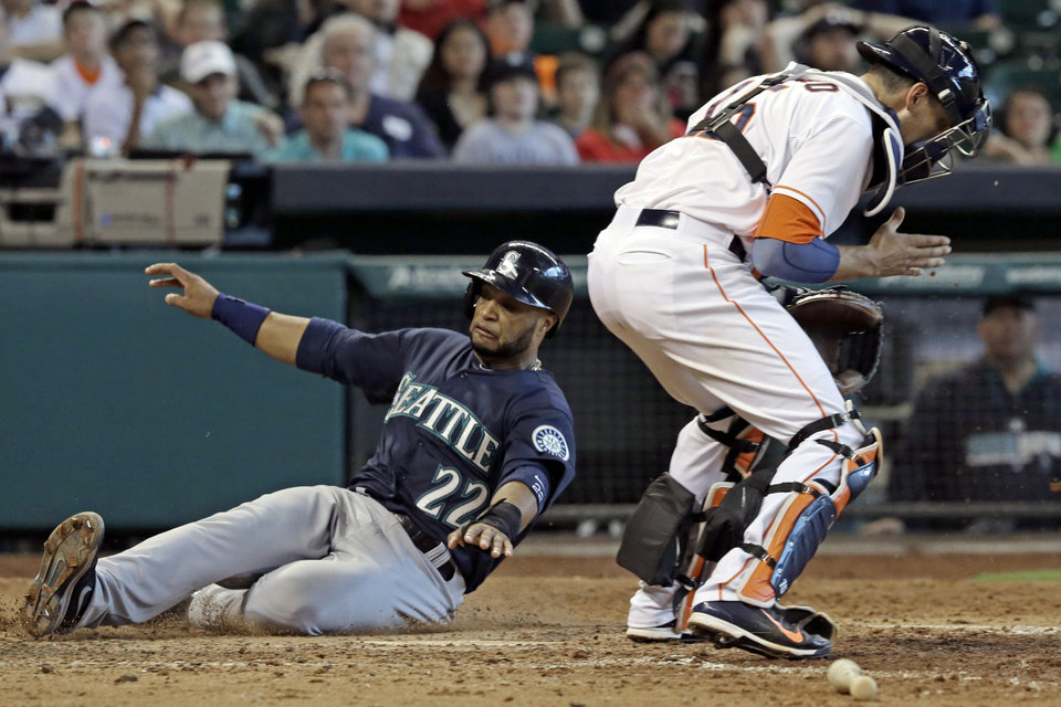 Photo - Seattle Mariners' Robinson Cano (22) is safe at home plate as Houston Astros catcher Jason Castro comes up empty-gloved in the seventh inning of a baseball game on Saturday, May 3, 2014, in Houston. Cano scored on a Kyle Seager double. (AP Photo/Pat Sullivan)