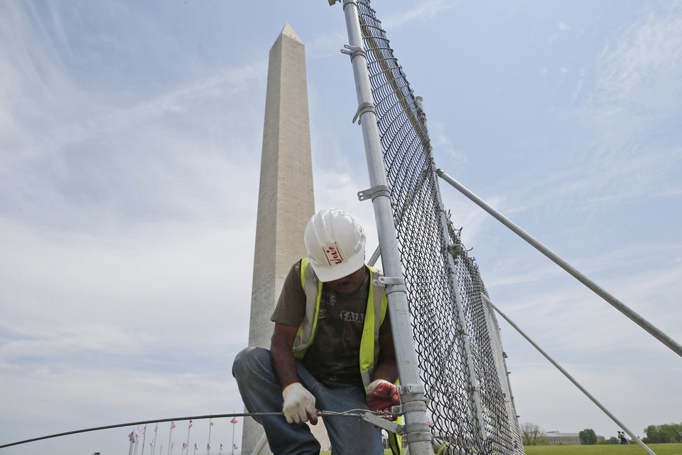 Photo - In this Friday, May 9, 2014 photo, worker Julio Dichis removes the fencing which closed the Washington Monument off to the public during renovations, in Washington. The monument, which sustained damage from an earthquake in August 2011, will re-open to the public on Monday, May 12, 2014. (AP Photo/Charles Dharapak)