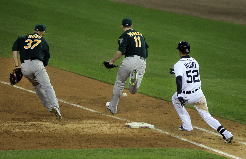 Photo -   Detroit Tigers Quintin Berry (52) reaches first base as Oakland Athletics starting pitcher Jarrod Parker (11) and first baseman Brandon Moss (37) chase the grounder during the third inning of Game 1 of the American League division baseball series, Saturday, Oct. 6, 2012, in Detroit. The Tigers' Omar Infante scored and Parker was charged with a fielding error on the play.(AP Photo/Carlos Osorio)