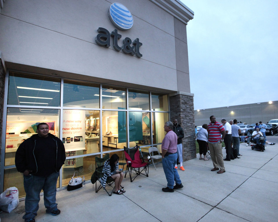 Photo - People wait in line for the new iPhones at the AT&T store on Memorial and Pennsylvania.  David McDaniel - The Oklahoman