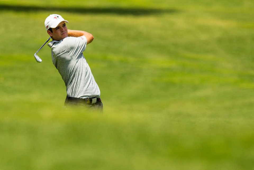 Photo - Corey Conners, of Canada, plays his second shot on the eighth hole during the quarterfinal round of match play at the U.S. Amateur Championship golf tournament at Atlanta Athletic Club in Johns Creek, Ga., Friday, Aug. 15, 2014.  (AP Photo/USGA, John Mummert)